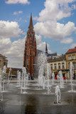 Osijek, Croatia - Nov 3, 2018: Scenic view of fountain on the main square and catholic St Peter and Paul Cathedral in the background.