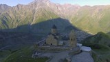 Aerial view. The Gergeti Church on background of Kazbek - 234082484