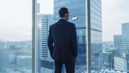 Shot of the Confident Businessman in a Suit in His Office, Put Hands in Pockets and Looking out of the Window Thoughtfully, Contemplating New Business Deals and Future Contracts.