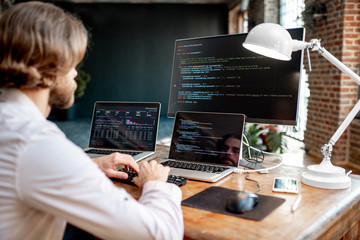 Young male programmer writing a program code sitting at the workplace with three monitors in the office. Image focused on the screen