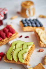 Assortment of healthy fresh breakfast toasts. Bread slices with peanut butter and various fruits and ingredients on side. Placed on white wooden table. Top view, with copy space. Selective focus