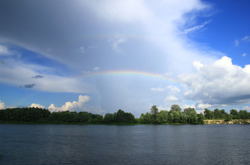 Wonderful rainbow over the river Desna in Ukraine, heavy clouds contrasts to clean part of the sky, deep shadow from cloud contrasts to shining sun in the part of scene. Storm is coming