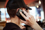 A young man in a cap, talking on a mobile phone - 234136879