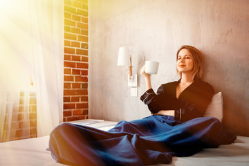 Style white woman sitting in bed with cup of coffee and thinking about something at home in morning