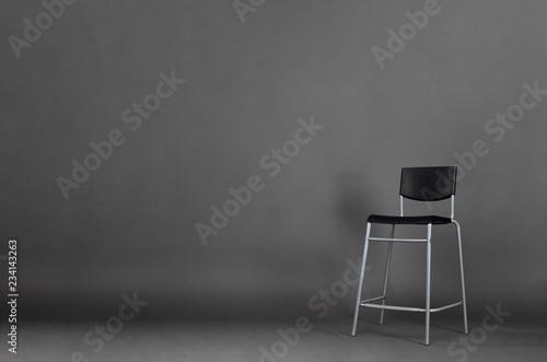 Czarny metalu krzesło odizolowywający na popielatym tle z kopii przestrzenią w studiu.