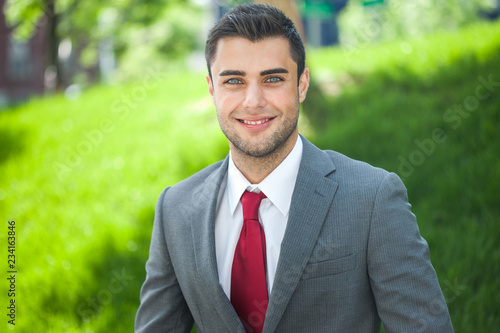 Leinwanddruck Bild Portrait of a young handsome businessman relaxing in a park