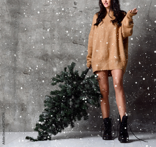 Leinwandbild Motiv Beautiful woman with Christmas fir tree in sexy knitted sweater blouse under snow