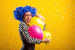 Colorful fun portrait of woman with balloons and confetti in front of yellow background