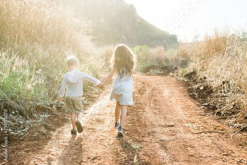 Leinwandbild Motiv Brother and sister running together at a farm