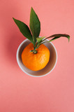 Mandarin in a white Cup on a pink background