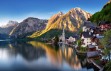 Classic postcard view of famous Hallstatt lakeside town reflecting in Hallstattersee lake in the Austrian Alps in scenic morning light on a beautiful sunny day in summer, Salzkammergut region, Austria - 234228407