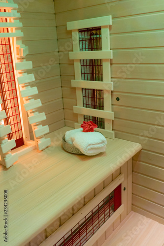 Leinwanddruck Bild Wooden bench in an infrared cabin with white towel and blossom