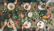Leinwandbild Motiv Traditional Christmas, New Year holiday celebration. Flat-lay of friends or family eating various food at festive table with turkey or chicken, vegetables, mushroom sauce, fruit, top view
