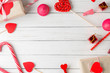 Valentines day background. Frame of red hearts, gift box with ribbon and candy sweets on a white wooden background, top view