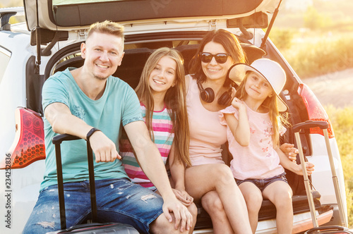 Leinwandbild Motiv Mum and dad with daughters in the opened car trunk with suitcase