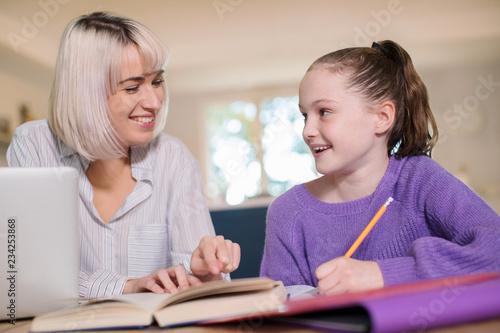 Leinwandbild Motiv Female Home Tutor Helping Young Girl With Studies