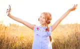 Smiling teenage girl hold smartphone and listening to music with joyfully raised hands in the field - 234255419