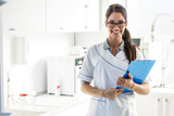 Portrait of female dentist .She standing in her dentist office.