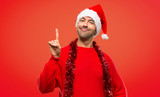 Man with red clothes celebrating the Christmas holidays showing and lifting a finger in sign of the best on red background