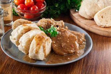 Pork loin in gravy with bread dumplings and sauerkraut