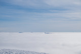 Above white heavy clouds. Panorama of cloudscape from the top of the mountain.