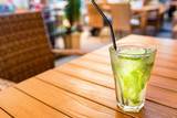 Mojito cocktail with lime on wooden table with blurred restaurant background
