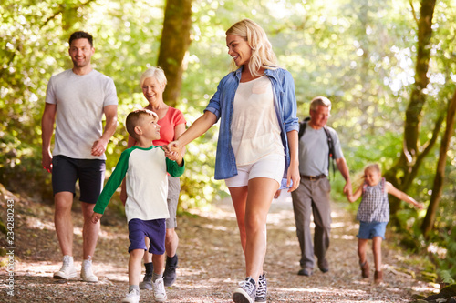 Multi Generation Family Enjoying Walk Along Woodland Path Together - 234280243