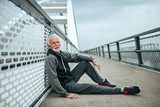 Portrait of a senior sportsman relaxing after a run. Sitting on city bridge, looking at camera. © bnenin