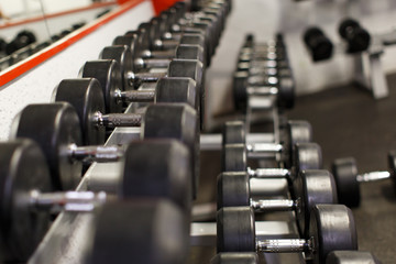 Sports equipment steel dumbbells on shelf