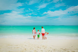 happy family with three kids walk on beach