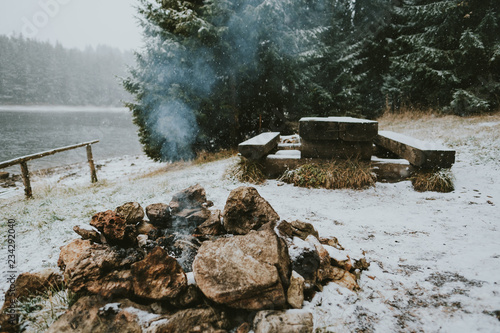Fire near snowy lake and forest