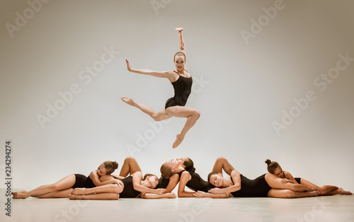 The group of modern ballet dancers dancing on gray studio background © master1305