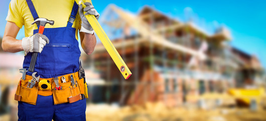 worker with tool belt in house construction site