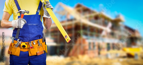 pracownik z paskiem narzędzi w budowie domu