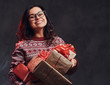 Portrait of a happy brunette girl wearing eyeglasses and warm sweater holding a gifts boxes, isolated on a dark textured background.