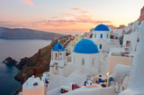 townscape of Oia, traditional greek village of Santorini, with blue domes of churches at sunset, Greece