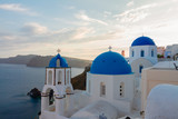 traditional white greek village Oia of Santorini, with blue domes of churches in sunset light, Greece - 234358013