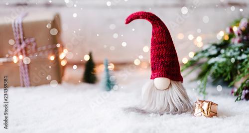 Leinwanddruck Bild Frohe Weihnachten - Kleiner Wichtel zwischen Geschenken, Schnee und weihnachtlicher Dekoration im Winter