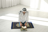 Muslim man with Koran praying on rug indoors