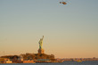 Helicopter flying over the Statue of Liberty just before Sunset