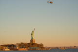 Helicopter flying over the Statue of Liberty just before Sunset © david