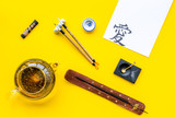 Lesson of calligraphy concept. Paper with hieroglyph near writing accessories, teapot and cup of tea on yellow background top view