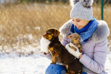 Woman playing with dogs during winter © anetlanda