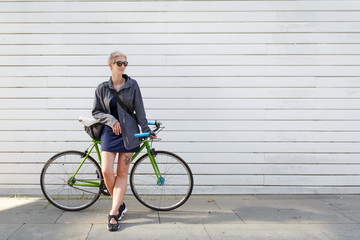 Full-length photo of young blonde with green bike near grey wall