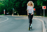 Full-length photo of curly-haired athletic woman kicking on scoo - 234437876