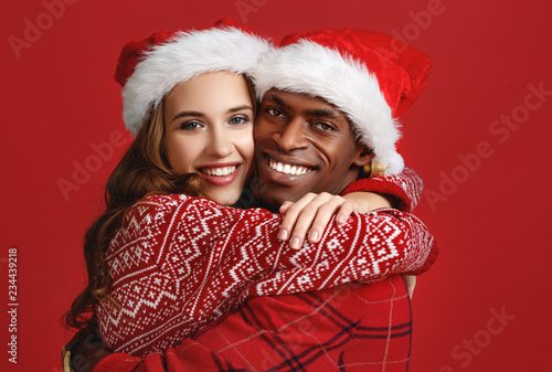 Leinwanddruck Bild happy couple black man and caucasian woman in christmas hats on red background