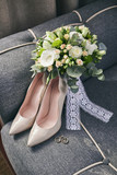 bridal accessories such as shoes, rings and bouquet  lie on a sofa