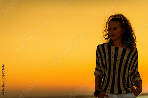 fototapeta na ścianę young woman on seacoast in evening looking into distance
