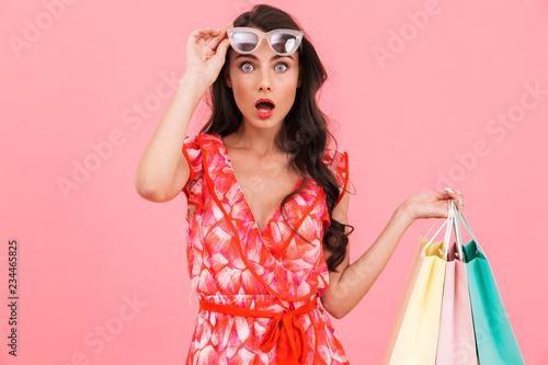 Leinwandbild Motiv Shocked Lady posing isolated over pink background wall holding shopping bags.