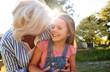 Leinwandbild Motiv Grandmother Playing Game With Granddaughter In Summer Park
